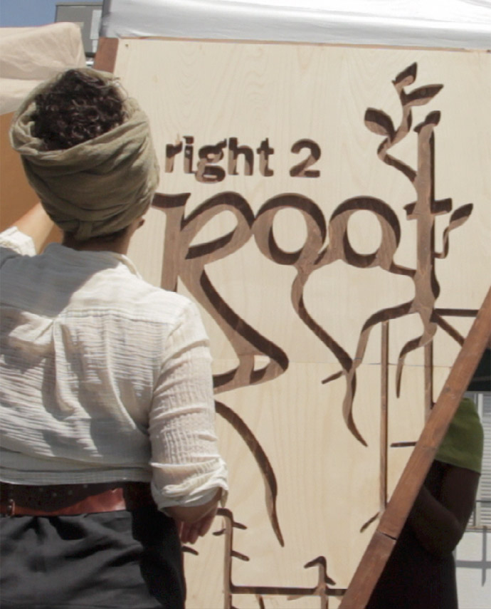 Woman with her back turned, standing in front of Right2Root wooden sign